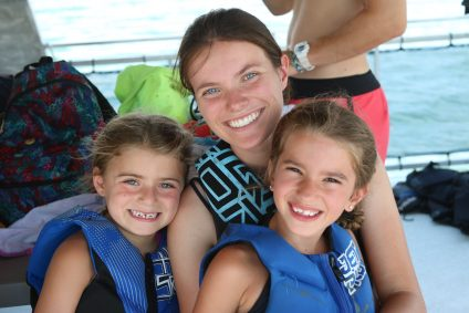 a woman and two children in life jackets smiling