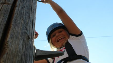 young girl climbing a pole smiling down at camera